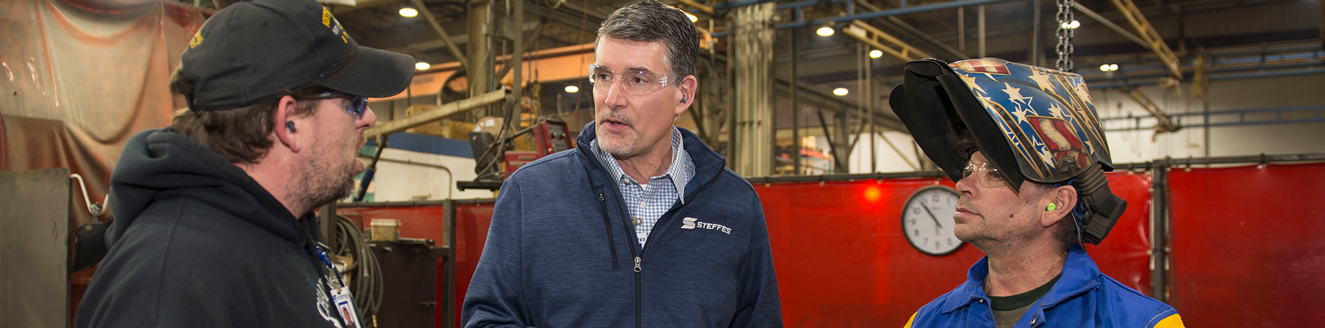 Paul Eidenschink talking to two Steffes employees on the manufacturing plant floor