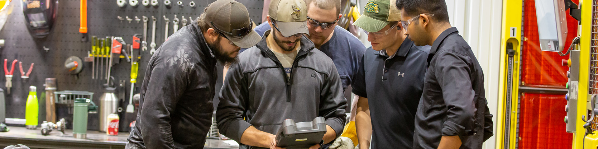 Five Steffes engineers looking at a controller for a robot at a manufacturing facility