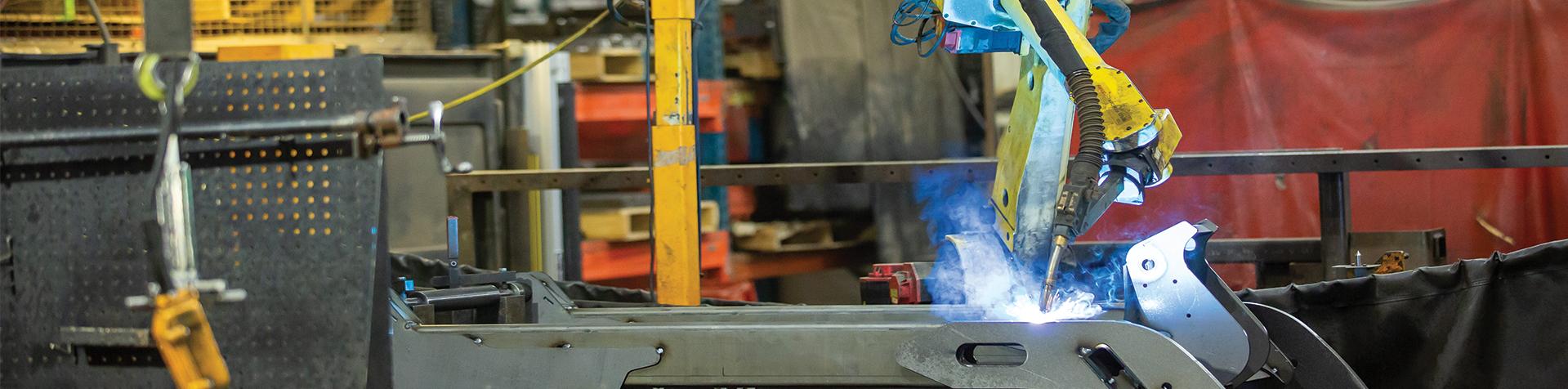 A welding robot welding a piece of metal at a Steffes manufacturing plant