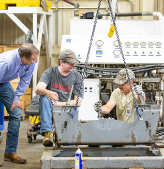 A photo of three Steffes employees assembling an attachment for a contract manufacturing partner on the factory floor