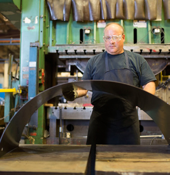 A photo of a Steffes manufacturing employee working with a piece of sheet metal on the production floor