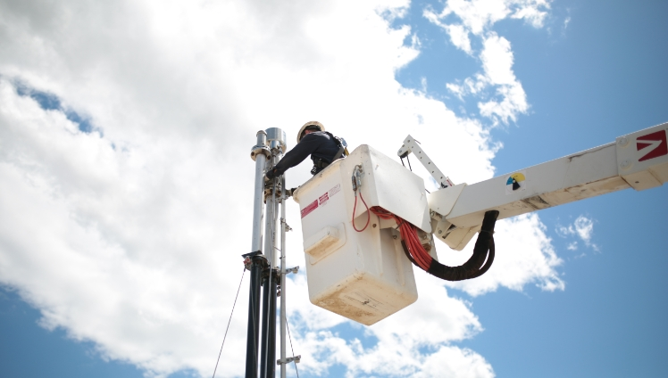 A photo of a Steffes Energy Services Technician conducting maintenance on a flare using a bucket truck
