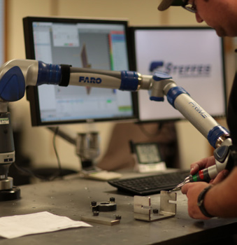 A photo of a Steffes engineer working with a robot to manufacture a stainless steel product
